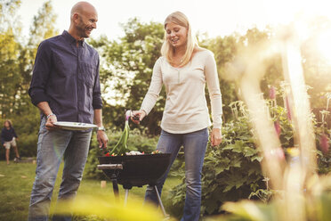 Happy father and daughter cooking vegetables on barbecue grill in back yard - MASF02426