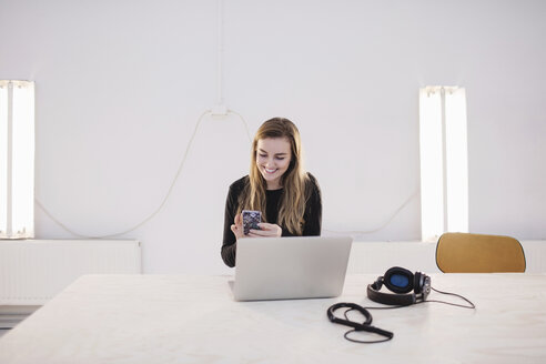 Happy female blogger using smart phone at desk in office - MASF02432
