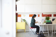 Full length side view of businesswoman with document and laptop at table in office - MASF02435