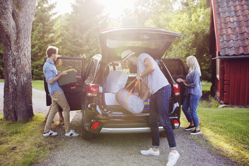 Full length of friends loading luggage into car on road during sunny day - MASF02465