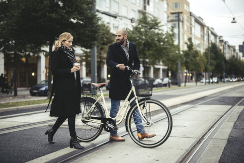 Full length of business people with bicycle crossing city street - MASF02477