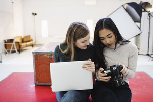 Female bloggers watching photographs on digital camera in office - MASF02480