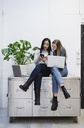 Female bloggers using smart phone while sitting on sideboard in creative office - MASF02483