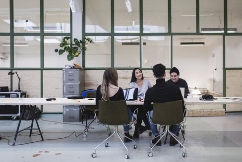 Four people discussing at desk in creative office - MASF02489