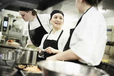 Female chef cooking food while talking with colleague in commercial kitchen - MASF02492