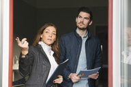 Female realtor and young man standing by window while pointing away - MASF02495
