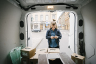 Female worker using mobile phone with cardboard boxes in delivery van - MASF02498