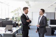 Two businessmen standing in office, discussing solutions - DIGF03885