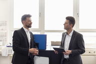 Two businessmen standing in office, discussing solutions, using digital tablet - DIGF03891