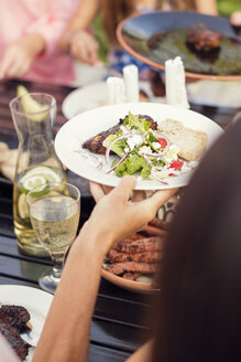 Cropped hand of woman holding food plate over dining table in back yard - MASF02508