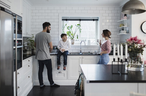 Father and mother with son in kitchen at home - MASF02514