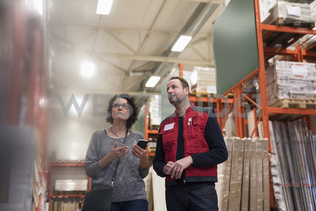 Customer holding smart phone while standing with salesman in hardware store - MASF02523