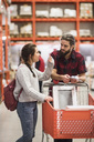Couple discussing while standing with shopping cart in hardware store - MASF02526