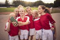 Cheerful soccer girls taking selfie on footpath against field - MASF02538