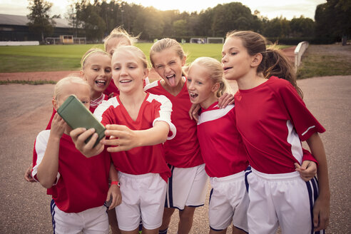 Cheerful soccer girls taking selfie on footpath against field - MASF02538