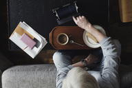 Directly above shot of senior man using digital tablet while having breakfast at home - MASF02544