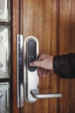 Cropped image of senior man opening electric lock on wooden door - MASF02547
