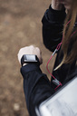 Cropped image of female athlete checking fitness tracker in forest - MASF02550