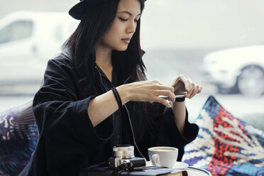 Young woman photographing coffee through smart phone in creative office - MASF02556