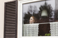 Woman looking through window while standing at home - MASF02562