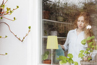 Woman watering potted plant at home seen from glass window - MASF02565