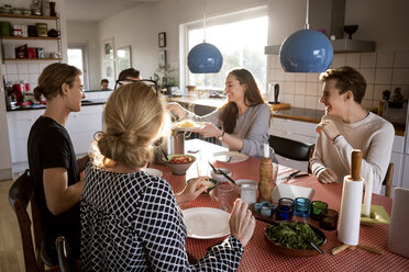 Woman serving food for family at dining table - MASF02580