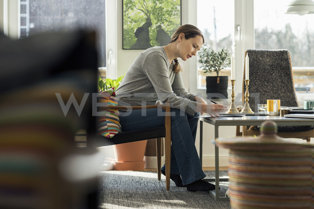Woman sitting with document at home - MASF02583