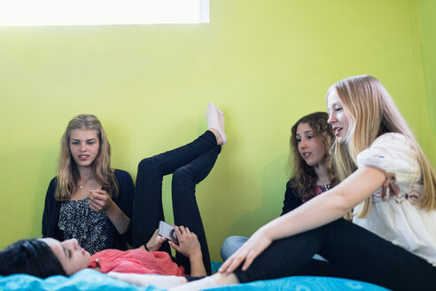 Teenage girls talking while relaxing on bed at home - MASF02598