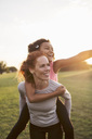Woman giving piggyback to daughter at park against sky during sunset - MASF02604