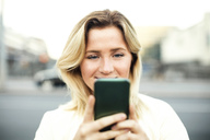 Young woman using mobile phone in city - MASF02622