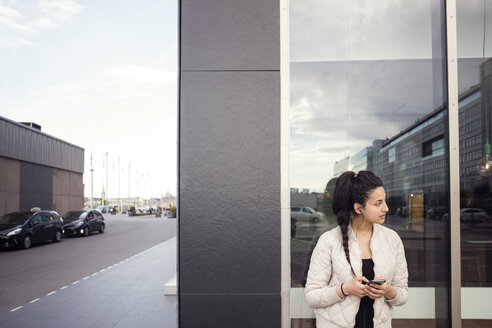 Young woman using smart phone while looking away against window - MASF02625