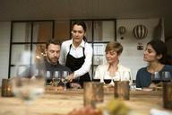 Woman wearing apron talking to business people while pointing at wineglass on table - MASF02628