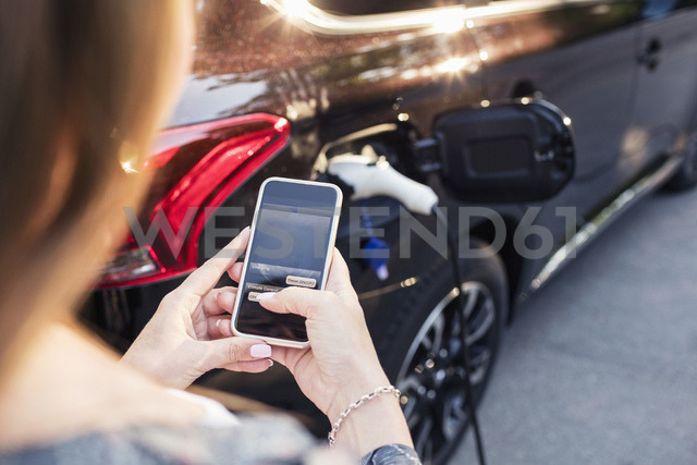 Woman using smart phone while standing by charging electric car - MASF02634