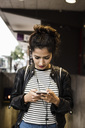 Woman listening music through smart phone in city - MASF02640