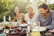 Cheerful couple and female friend laughing on dining table during garden party in back yard - MASF02643