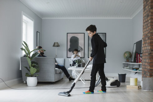 Boy vacuuming floor in living room at home - MASF02655