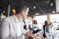 Businessman looking away while holding mobile phone at restaurant - MASF02658