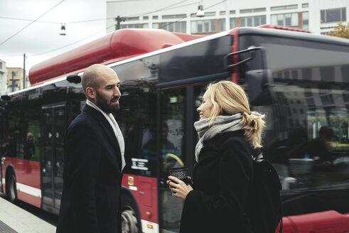 Business people talking on sidewalk by bus in city - MASF02670