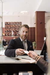Businessman giving credit card to receptionist at hotel reception - MASF02691