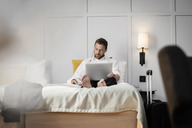Businessman sitting on bed using laptop against wall in hotel room - MASF02703