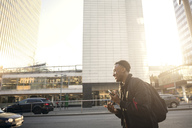 Smiling teenager gesturing while holding phone against buildings in city - MASF02736