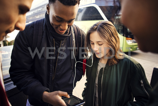 Teenage girl and boy listening music from smart phone while showing to friends in city - MASF02739