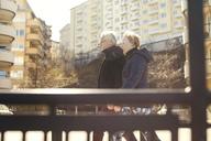Smiling senior couple walking on roadside against buildings in city - MASF02742
