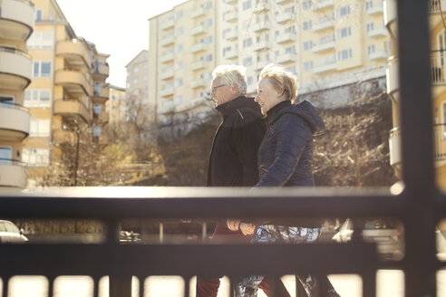 Smiling senior couple walking on roadside against buildings in city - MASF02742