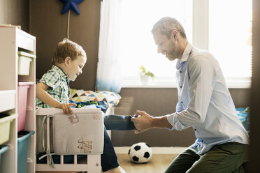 Smiling father dressing up son at home on sunny day - MASF02748