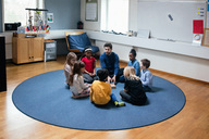 Teacher playing with students while sitting on floor at school - MASF02751