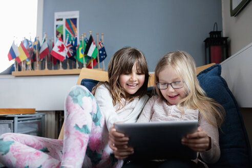 Smiling friends using digital tablet while resting on sofa in school - MASF02757