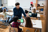 Teacher sitting on desk while explaining students using digital tablet in classroom - MASF02760