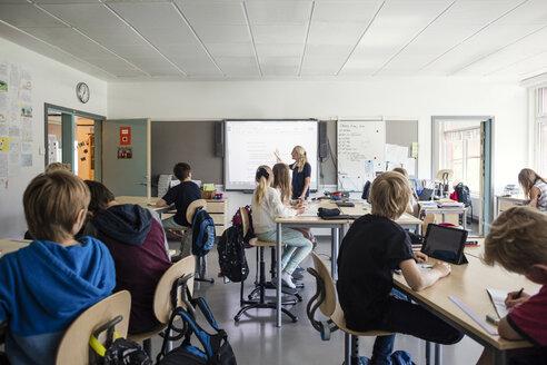 Teacher explaining students through whiteboard in classroom - MASF02772