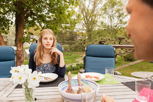 Teenage girl talking to father at table in yard - MASF02781